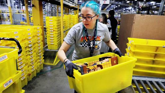 A worker moves a bin filled with products inside of an Amazon fulfillment centre in Robbinsville, New Jersey, November 27, 2017.